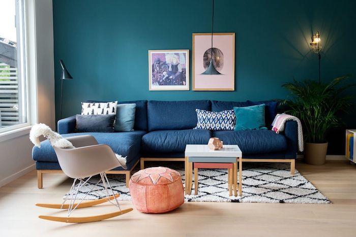 canapé en bleu classique et mur en bleu paon dans un salon scandinave cocooning avec chaise à bascule scandinave, pouf saumon, tapis noir et blanc