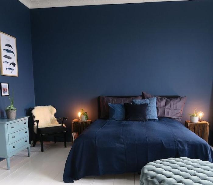 plafond et sol blanc et murs bleu nuit, coussins et oreillers bleu et marron, table de nuit en cagette de bois, idee deco chambre adulte homme