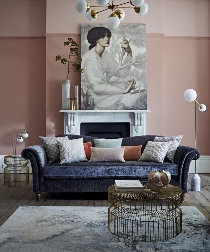 decoration salon 2020 aux murs rose pastel et sol en bois gris aménagé avec meubles en tissu bleu foncé et accents en métal