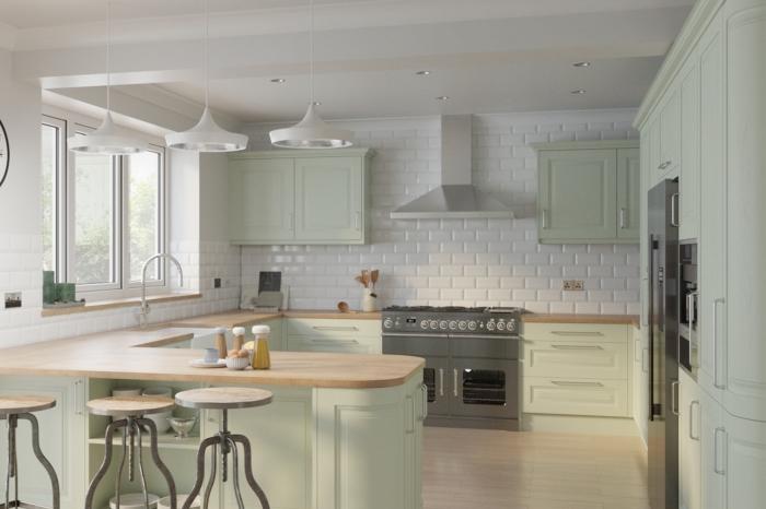 idée comment décorer une cuisine en U, modèle de cuisine aux murs en carreaux blancs avec comptoirs en bois et armoires vert pastel