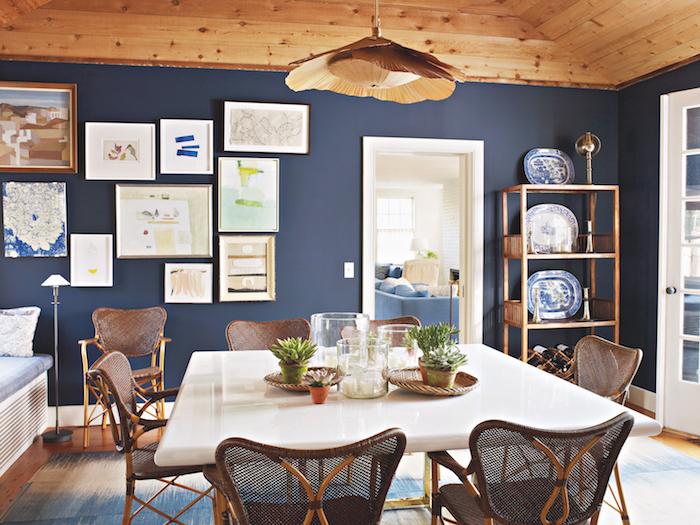 plafond bois dans une salle à manger contemporaine avec des chaises cannées et table blanc et laiton, deco murale de cadres art contemporain, suspension bois luminaire
