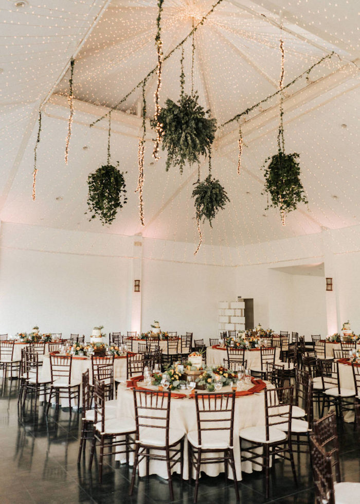 pots de plantes vertes retombantes suspendues et plafond décoré de guirlandes lumineuses au dessus de tables en nappes blanches et chaises bois et blanc sur sol carrelage noir