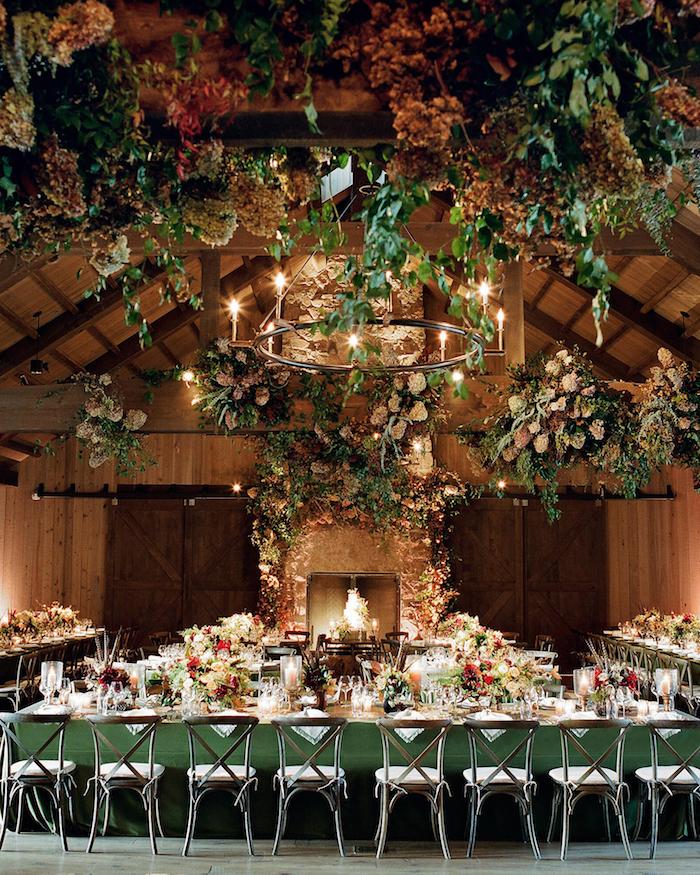 mariage dans vieilles granges boisées avec décoration plafond florale, cheminée mariage et tables en vert fleuries