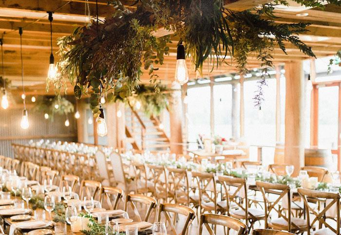 suspensions ampoules industrielles et déco florale de feuillages au dessus de table et chaises de bois et petite deco aux feuillages verts
