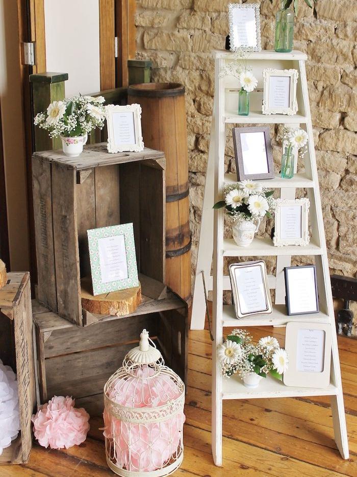 echelle deco originale avec échelle blanche décoré de plan de table mariage petites listes encadrées, cagettes deco vintage