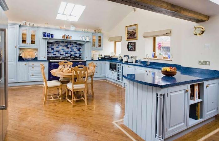 meuble cuisine couleur bleu ciel et plan de travail bleu foncé, parquet bois clair, poutre apparente, credence carrelage bleu