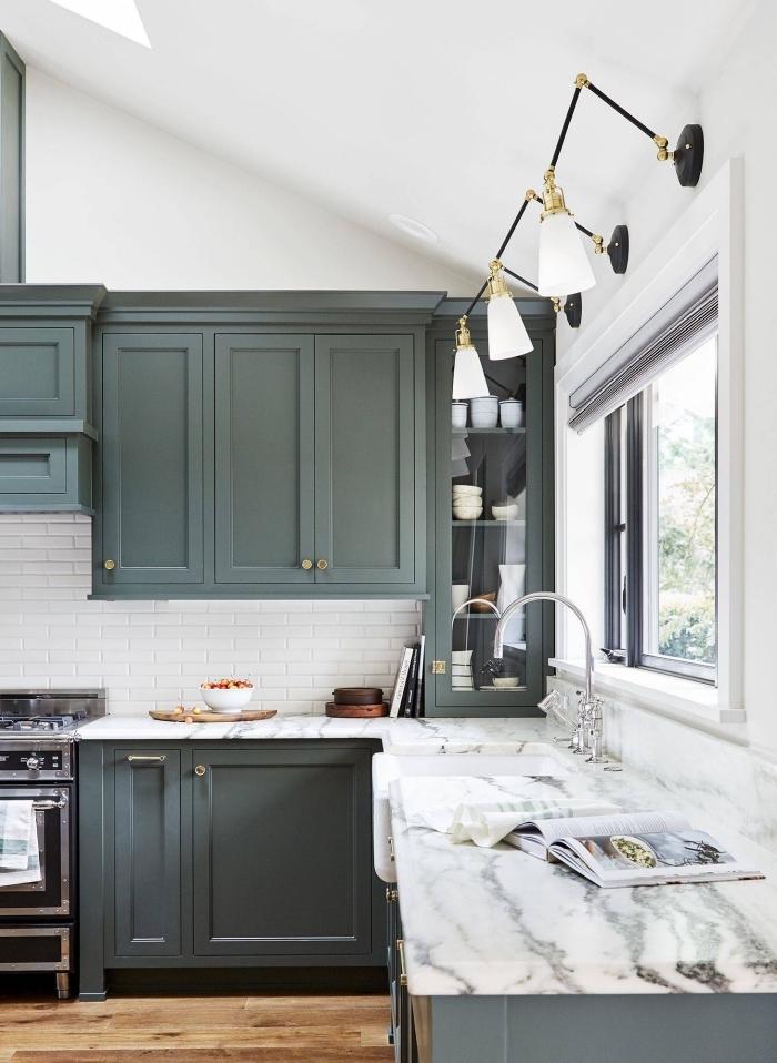 modèle de cuisine stylée aux murs blancs avec crédence carreaux blancs aménagée avec meubles de nuance vert de gris