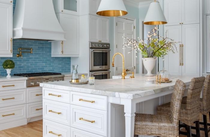 idee deco cuisine blanche avec accents en bleu et or, aménagement de cuisine en longueur avec îlot central