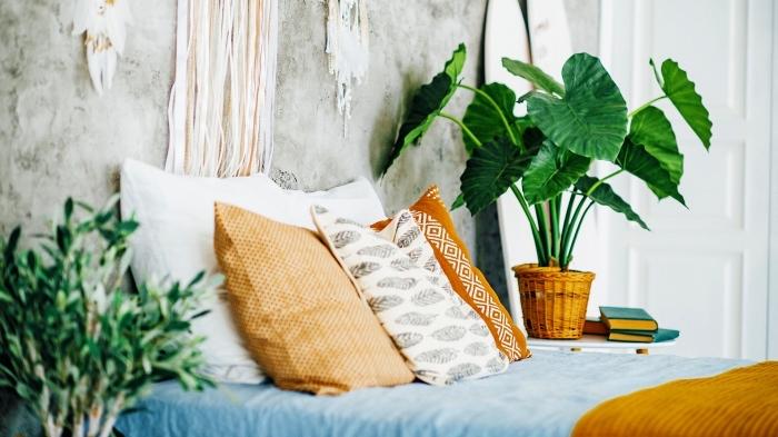 idée de déco de lit bohème chic avec coussins orange et blanc à motifs ethniques, décoration murale avec attrape-rêve