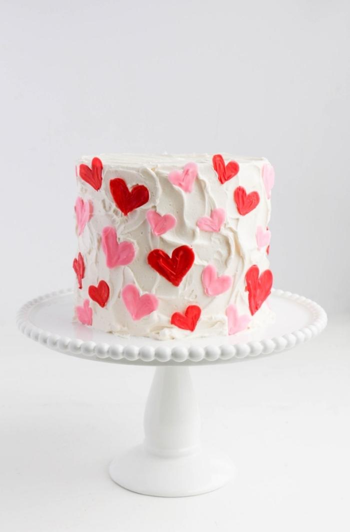 dessert fait maison pour un menu saint valentin romantique, modèle de gâteau rond au glaçage blanc avec coeurs décoratives rouges et roses