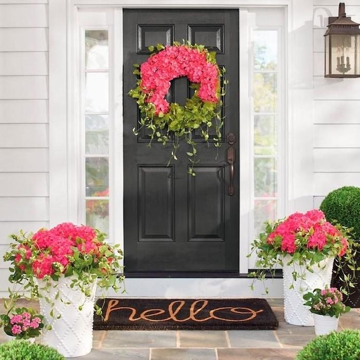 Murs blanches d'une maison avec porte d'entrée noire, couronne de fleurs pour dire bonjour à ses invités, idee deco de table romantique, inspiration décoration saint valentin