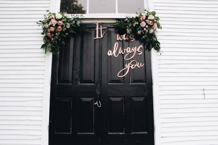 Porte noire décorée de fleurs, la meilleure idee deco soiree romantique, deco table st valentin