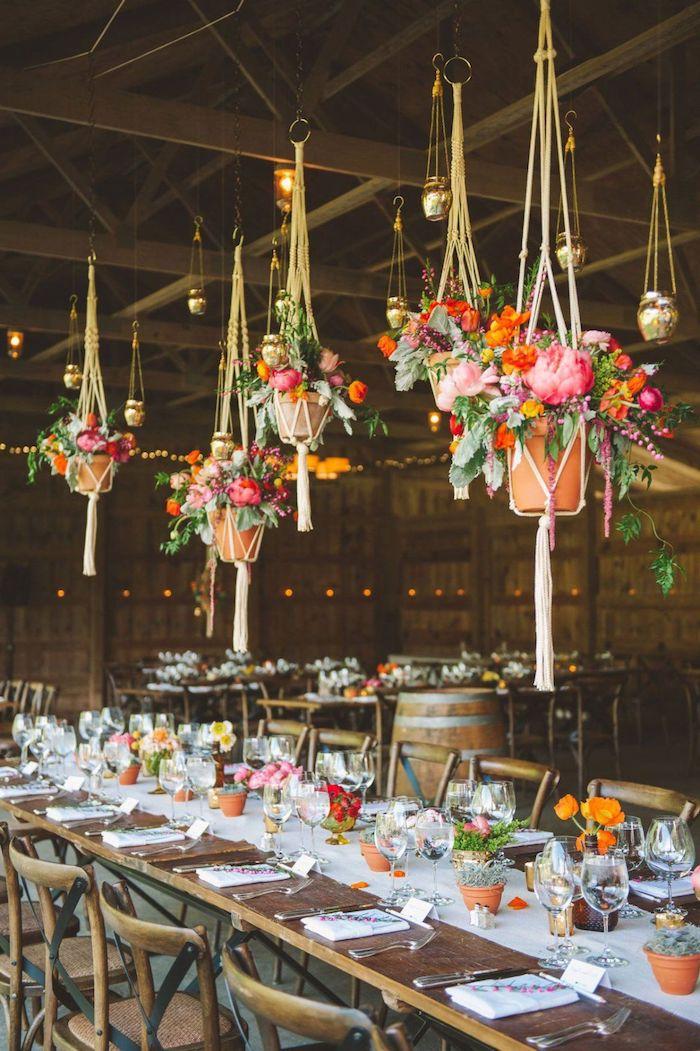 pots macramé suspendues avec des fleurs colorées au dessus de table et chaises bois, chemin de table blanc, petits pots de fleurs, idee deco mariage champetre chic