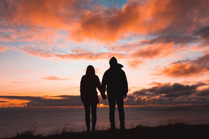 idée de sortie romantique pour la fête de la Saint Valentin, couple amoureux observant le coucher du soleil au bord de la mer