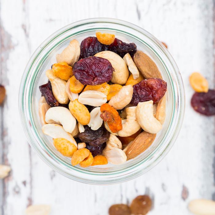 exemple de gouter simple a faire et sain constitué de noix variés et fruits séchés dans un pot en verre
