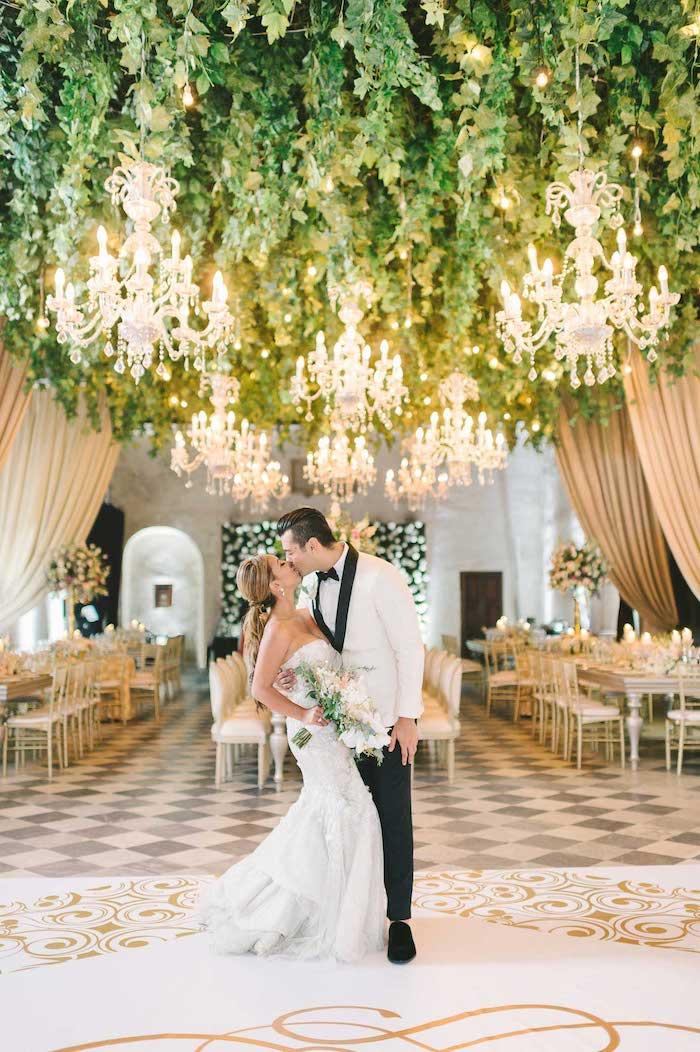 exemple de décoration plafond mariage en végétation verte et lustres élégantes au dessus de table et chaises blanches, carrelage damier gris et blanc