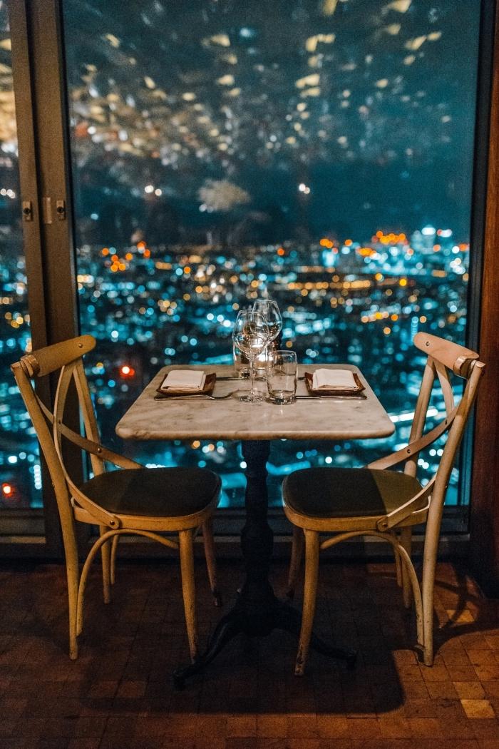 idée de sortie en couple, table à deux dans un resto à vue impeccable sur les lumières de la ville et le ciel nocturne
