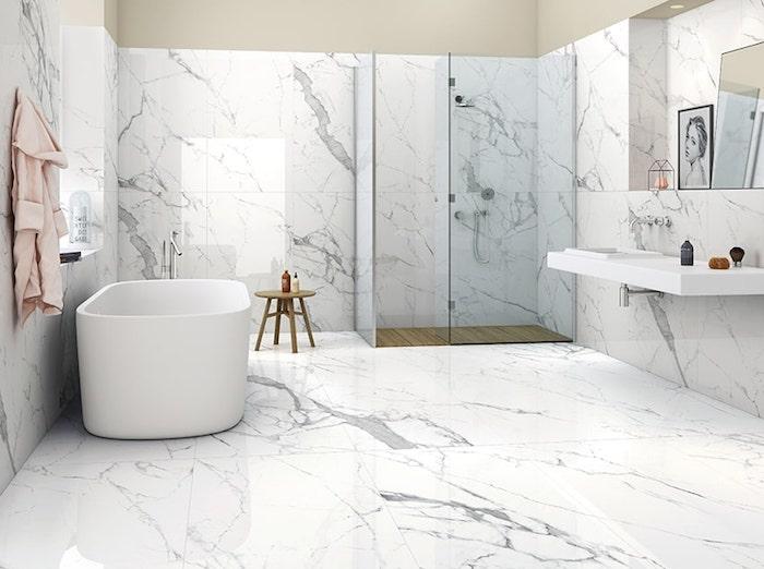 Baignoire ovale, chaise en bois pour ranger les nécessités pour le douche, salle de bain marbre blanc, cool idée comment décorer la salle d'eau