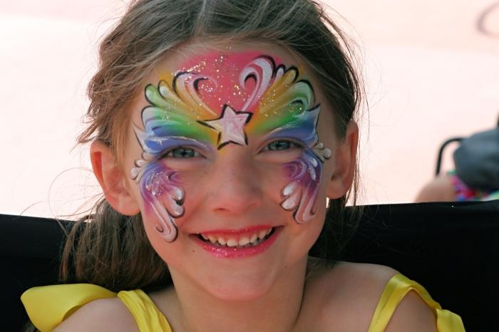 dessiner un masque de carnaval sur un visage d'enfant avec des peintures pour visage en couleurs arc en ciel