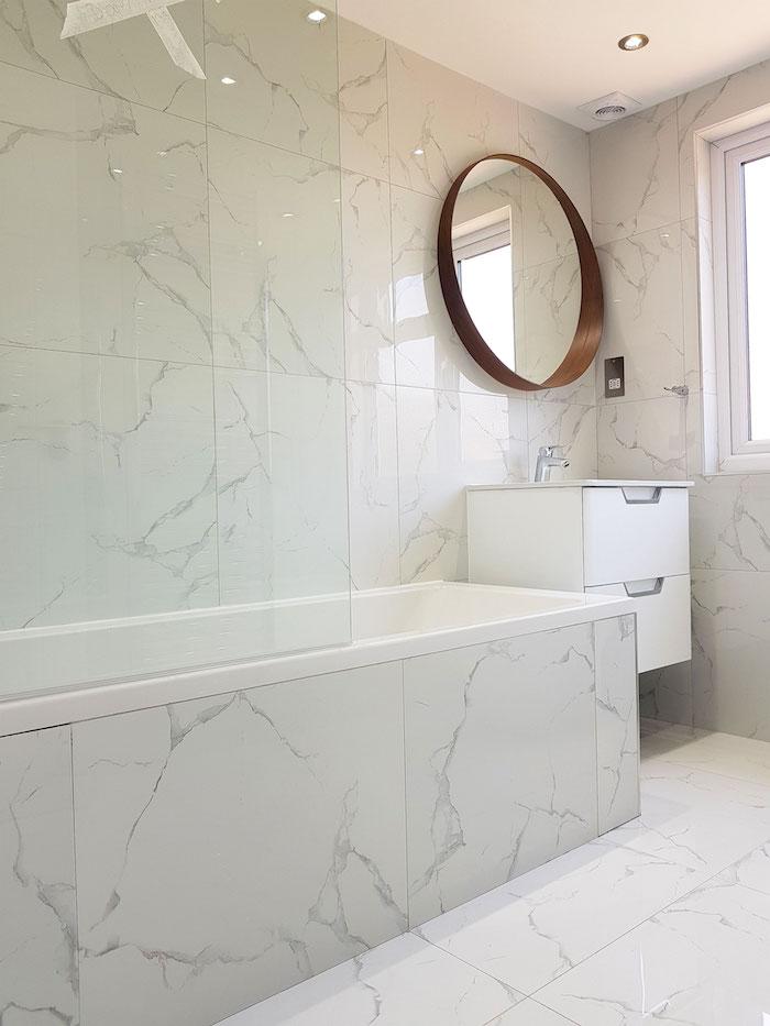 Rond miroir bois, meuble lavabo blanc laqué, salle de bain en marbre, intérieur salle de bain marbre blanc, baignoire en marbre avec viterine