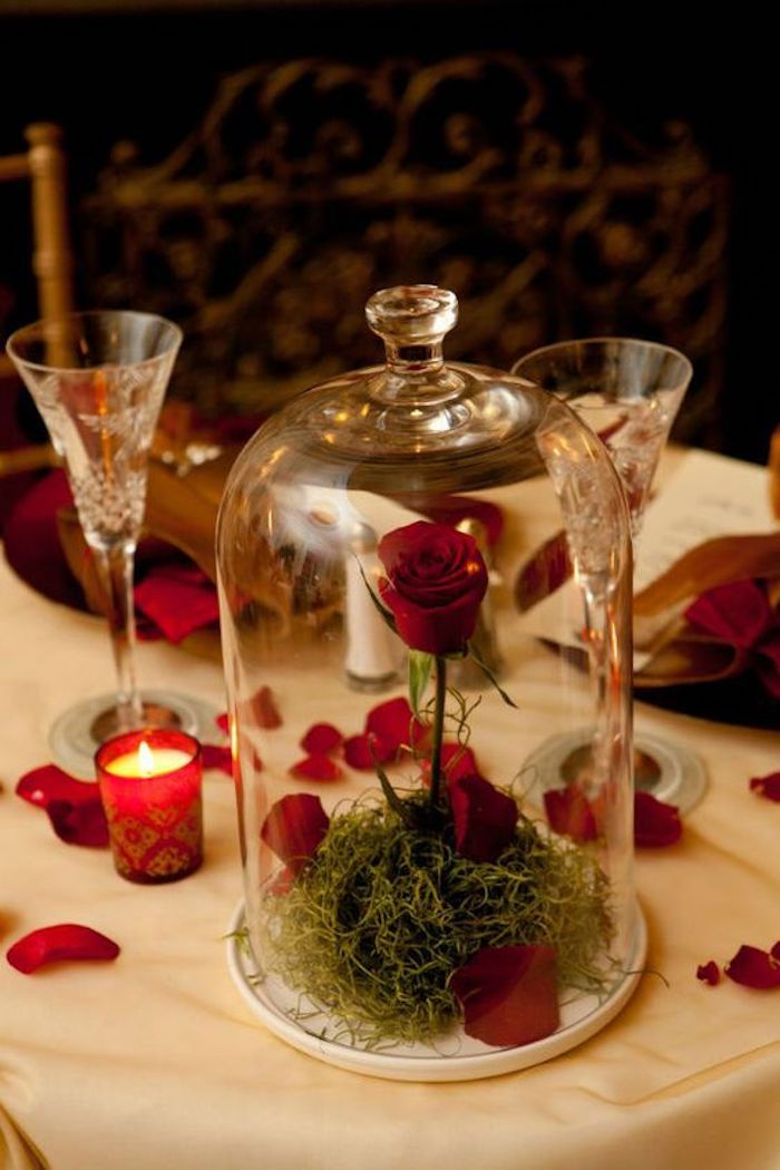 Table avec nappe blanche et cloche avec rose rouge, bougie et petales décoration de saint valentin, préparer une surprise pour ma copine