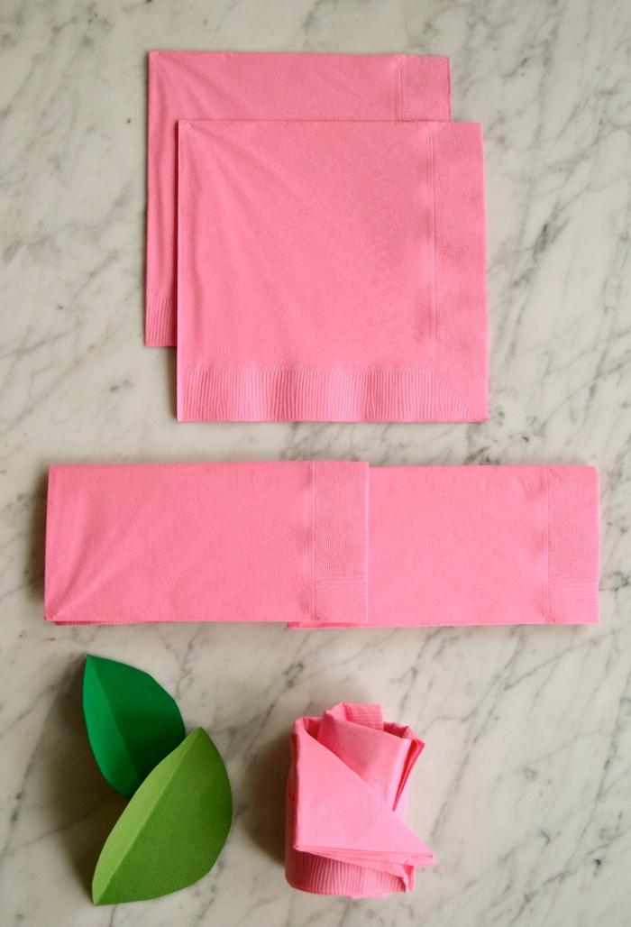 exemple de pliage de serviette en papier facile fleur, modèle de rose en deux serviettes roses avec feuilles vertes