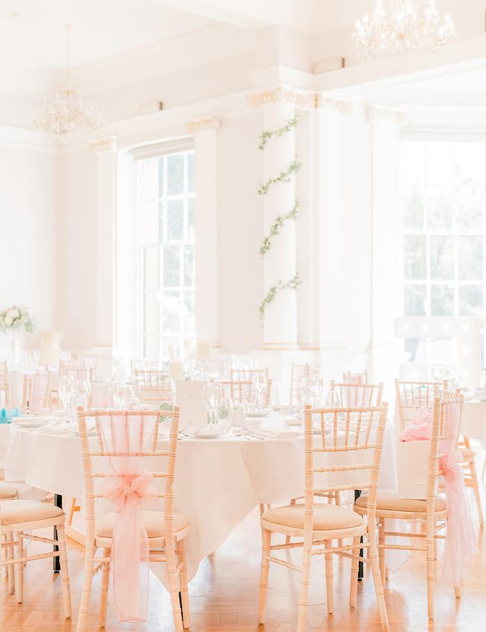 déco chaise de mariage en rubans rose, tables décorés de blanc avec verres transparentes, deco colonne de guirlande feuillage