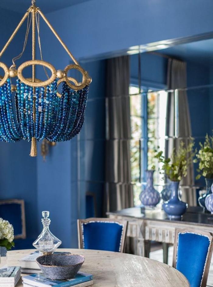 modele de salle a manger contemporaine aux murs bleus, table salle à manger bois brut, chaises bleues, vase avec des branches vertes