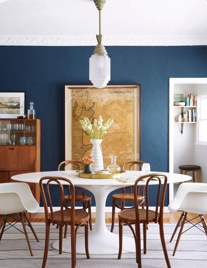 table salle à manger blanche entourée de chaises de bois, murs bleus, avec deco mappemonde vintage, vaisselier bois vintage, parquet bois clair