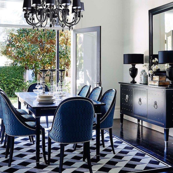 tapis noir, gris et blanc dans salle à manger vintage, table et chaises bleues, commode bleue, lustre elegant