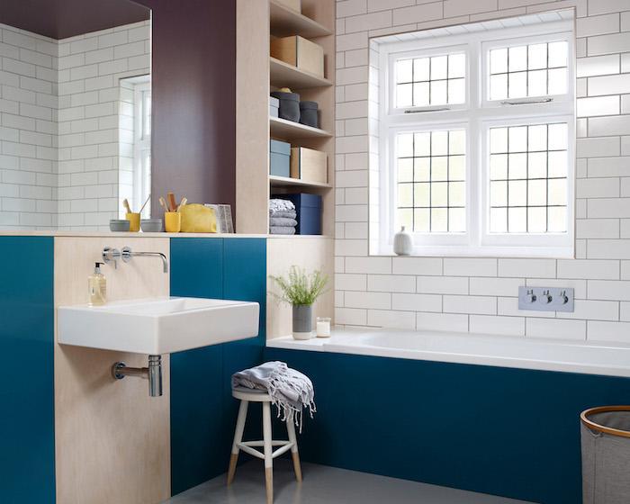 peinture bleue pour baignoire et mur, et pan de mur couleur bordeau, robinet blanc, carrelage mural blanc
