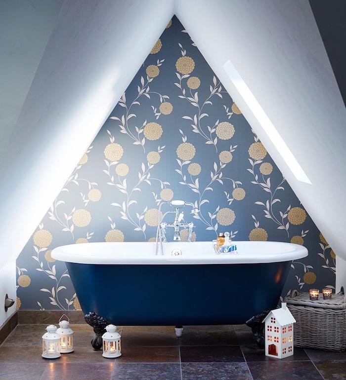 modele de salle de bain sous comble avec baignoire bleue et mur de fond papier peint bleu à imprimé fleuri, carrelage sol gris anthracite