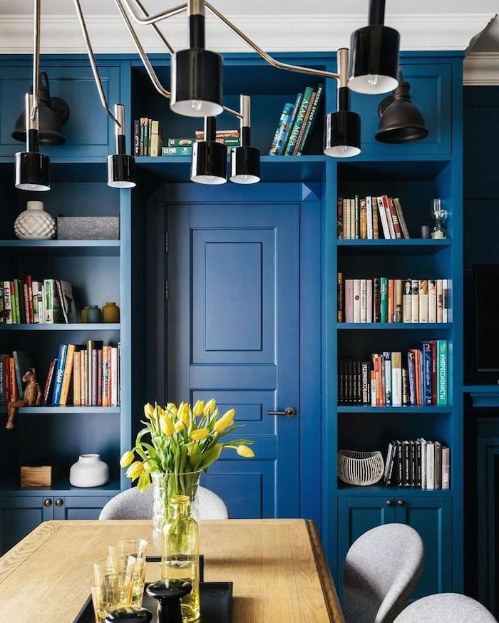 murs et porte de couleur bleue, petite bibliothèque à côté d une salle à manger avec table de bois et chaises grises