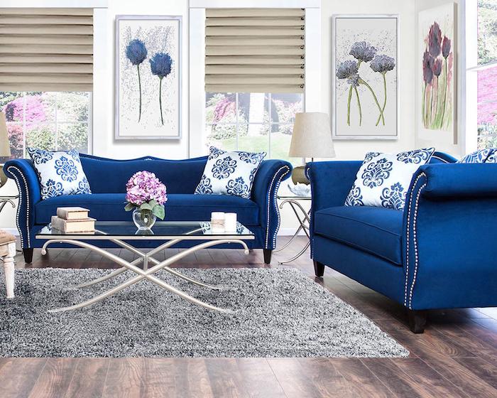 modele de canapé bleu nuit dans salon avec deco de cadres à motif fleur, tapis gris moelleux sur parquet salon