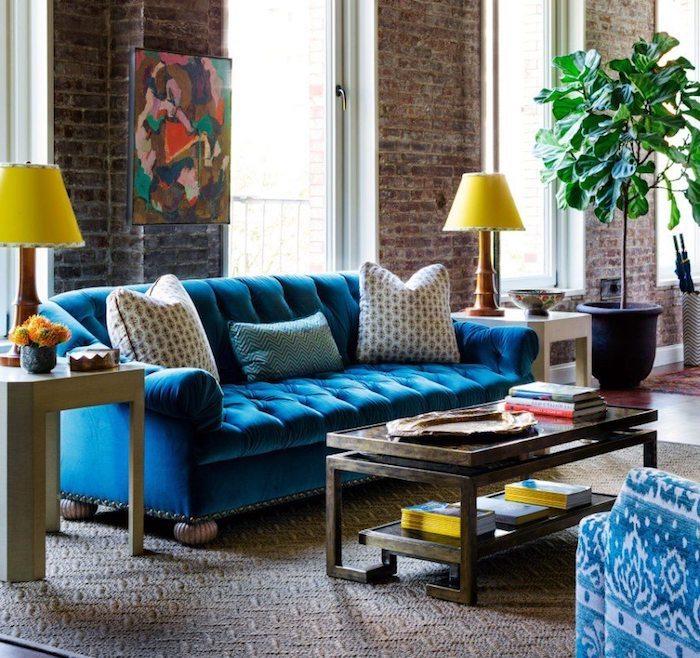 mur de briques et grandes fenetres dans salon style industriel avec canapé bleu et table bois originale sur tapis gris et blanc, plante verte en grand pot