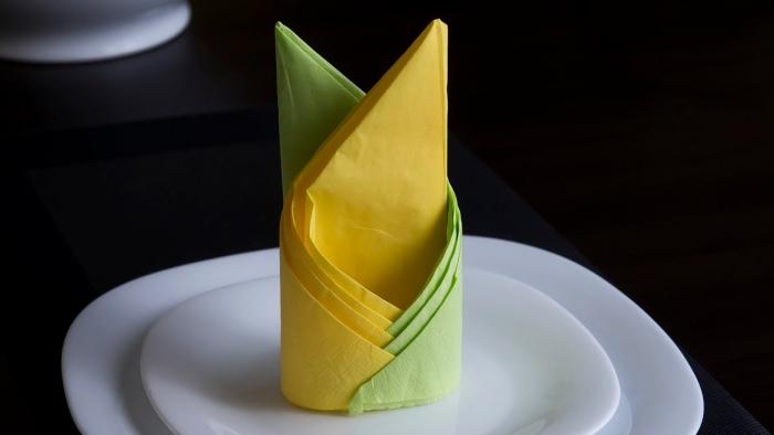 technique de pliage de serviette facile en deux couleurs, déco de table élégante avec assiettes rondes et serviette jaune vert