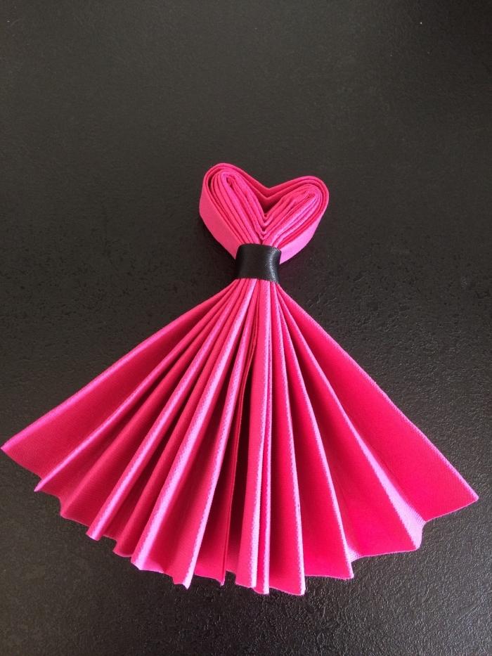 exemple comment plier une serviette en papier rose fuchsia en forme de robe de princesse à l'aide d'un ruban noir