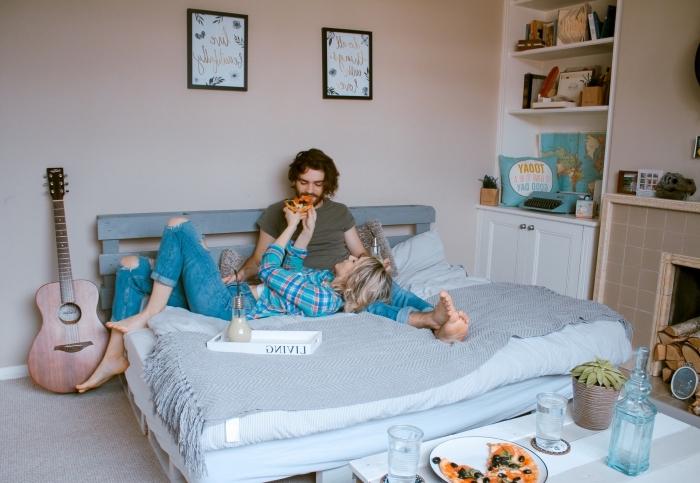 activités à faire en couple, chiller en couple avec un dîner au lit, garçon et fille amoureux mangeant du pizza au lit