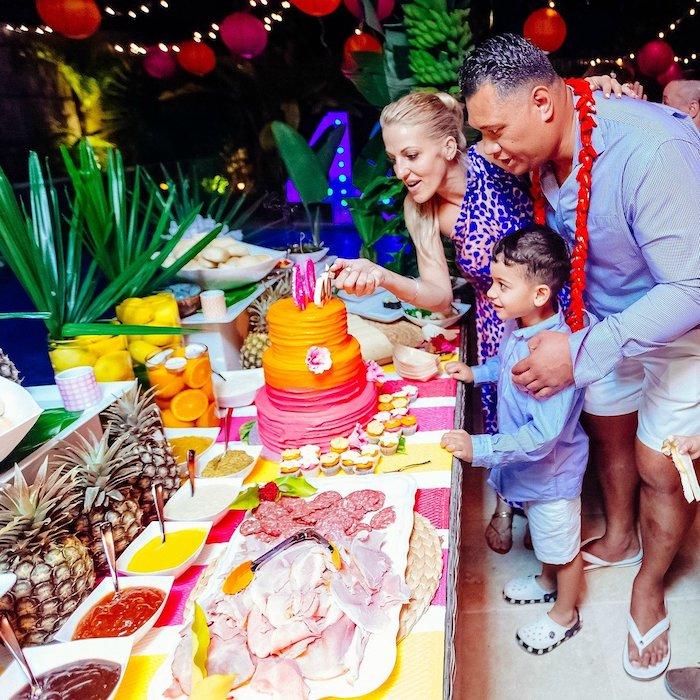 theme de soiree insolite, table décoré de nappe blanche à chemin jaune et rose, gateau coloré, accents deco fruit tropical