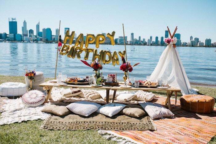 dcoration anniversaire adulte en plein air, deco anniversaire boheme chic avec table bois basse entourée de coussins, ballons dorés et tente blanche à coté