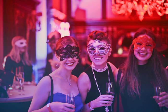 thème déguisement anniversaire bal masqué, femmes en robe de soirée chic et glamour et des masques de carnaval
