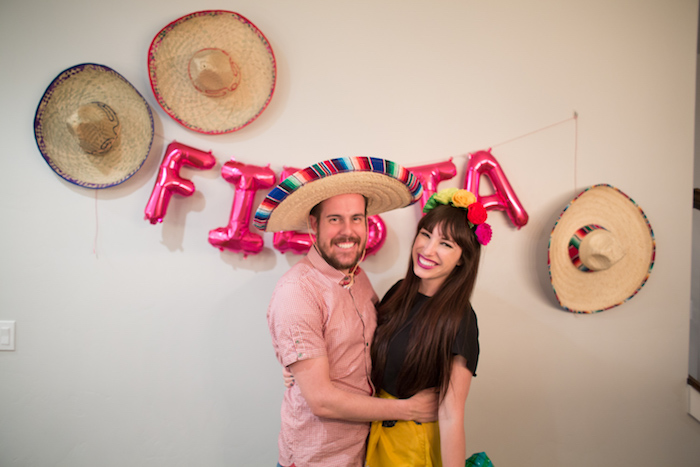 organiser une soirée mexicaine avec deco murale de chapeaux de paille, lettres ballons fiesta, femme et homme qui sourient