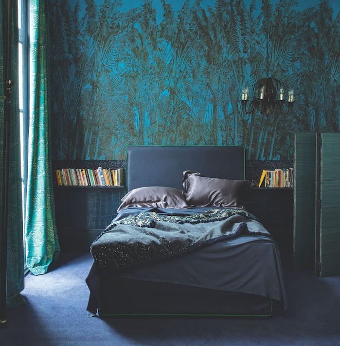 papier peint bleu à imprimé jungle dans une chambre à coucher gris et bleu avec rideaux verts et tapis bleu, lustre noir elegant