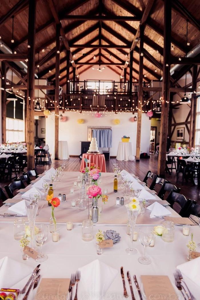 décoration de table mariage en petits soliflores sur nappe blanche, guirlande lumineuses pour décorer le plafond boisé avec poutres apparentes