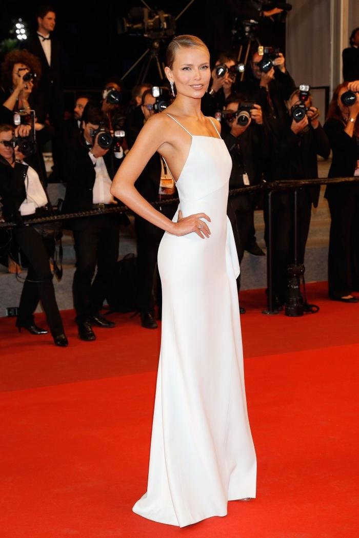 tenue de soirée gala pour femme en robe longue blanche avec bretelles fines, coiffure cheveux attachés en chignon