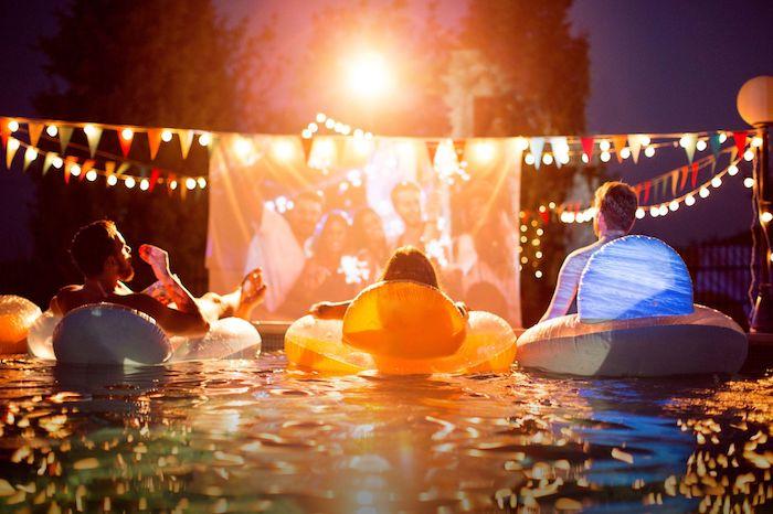 soirée cinéma piscine avec panneau cinéma et guirlande à fanions, idée thème soirée insolite