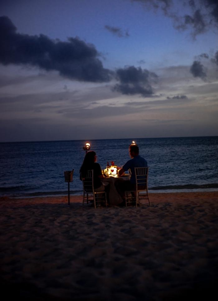 organiser un dîner surprise dans un endroit romantique, couple amoureux assis à table romantique sur la plage