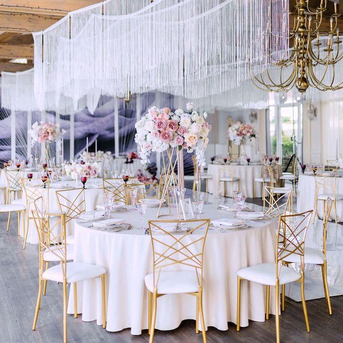 décorer le plafond mariage avec décoration chute de fils blancs au dessus de tables en nappes blanches entourées de chaises or et blanc avec bouquets de fleurs chic