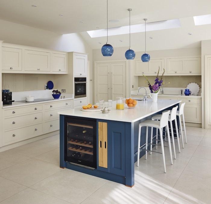 suspensions bleues au dessus d un ilot central cuisine bleu avec plan de travail blanc et chaises blanches, meuble cuisine blanc