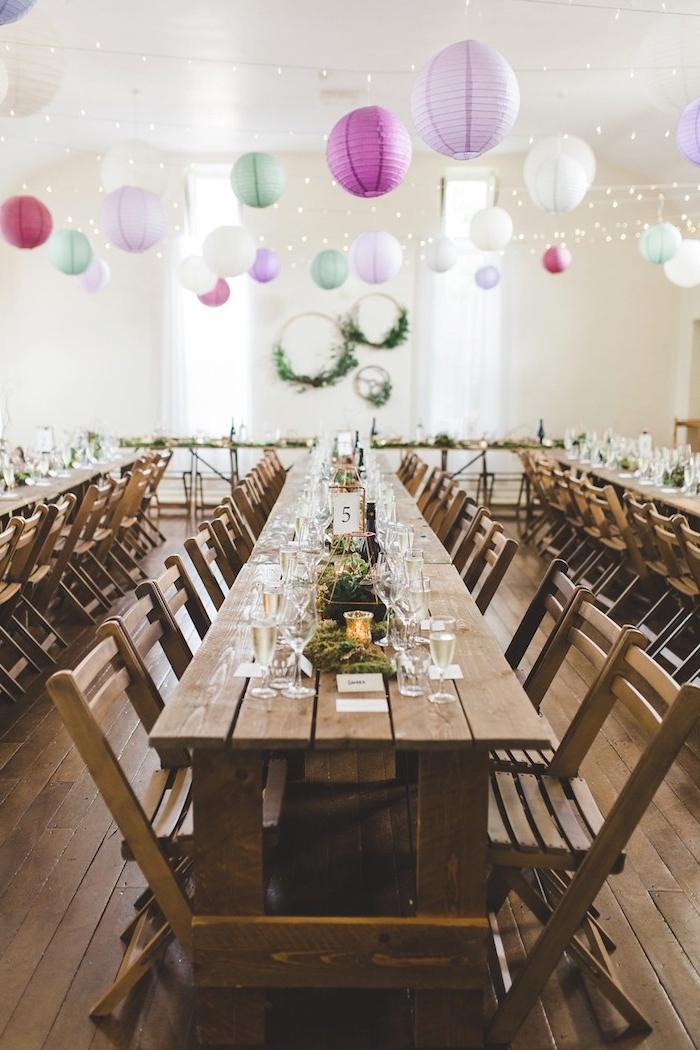 guirlande de lampions colorés géants et guirlande lumineuse en dessus, table et chaises bois brut, deco table mariage mousse florale et bougies